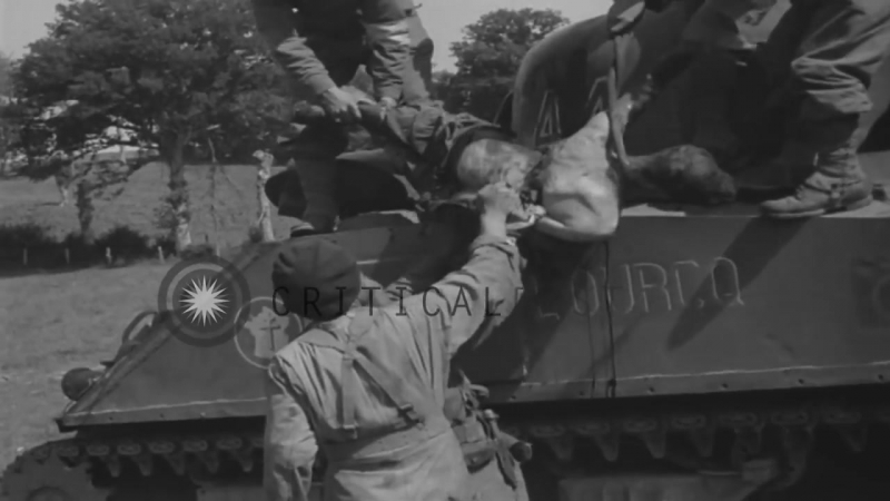French tank crew removing body of dead soldier from tank and laying him on blank