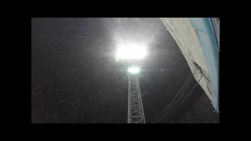 Снег падает в свете прожектора стадиона. FootageФутажи