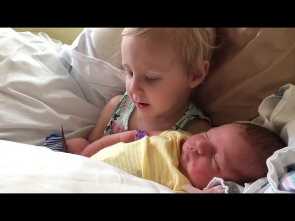 Toddler holds newborn baby brother - 989589