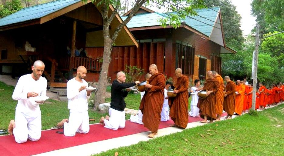 Тайские монахи получают еду из рук учеников