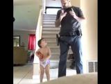 Отец учит совсем ещё маленького сына работе с пистолетом.?