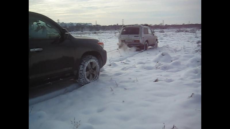 Нива тянет Крузака по снегу на нейтралке