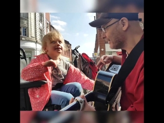 Seven year old blind girl plays the guitar with busker