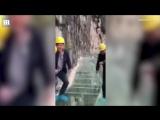 Китайские рабочие проверятют на прочность стеклянный мост