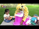 Animal costumes for kids: A big giraffe and little girl playing Cooking Toys in the Park.