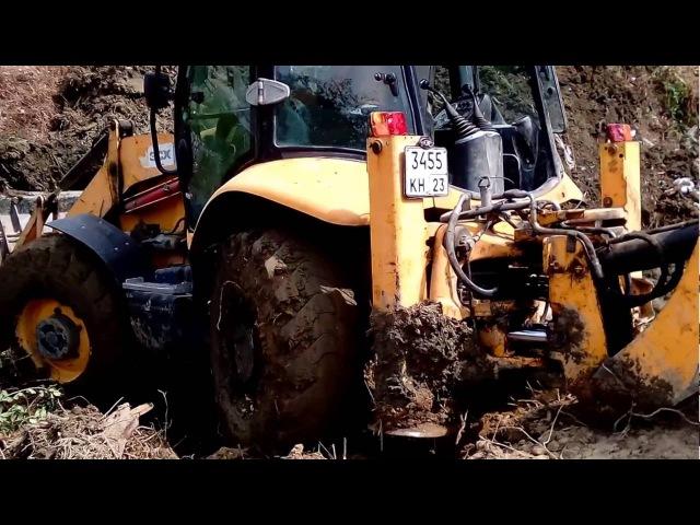 Экскаватор JCB 3CX Super выезжает из грязи