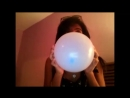 Girl blowing up a balloon with two hands until it pops