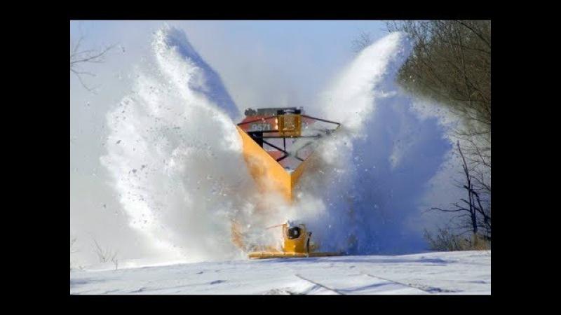 Снегоуборочные поезда мощно пробивают сугробы.