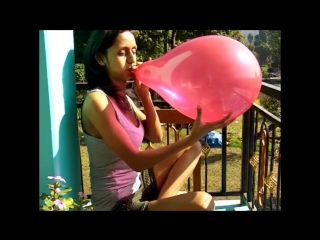 Girl blowing to pop balloon on a