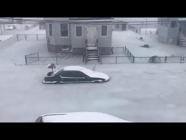 Frozen floodwaters form street of solid ice near Boston