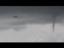 самолет летит рядом со смерчами в Сочи