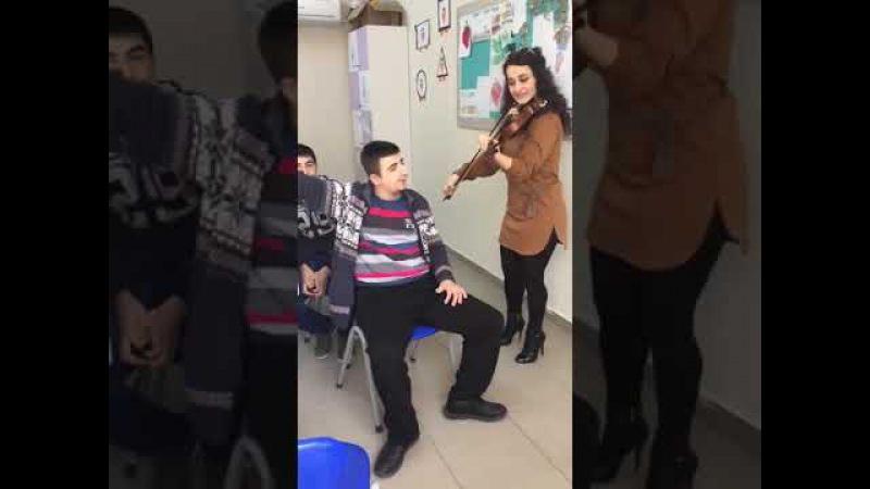 Otizmli müziğe aşık öğrencisine kemanı ile eşlik eden öğretmen