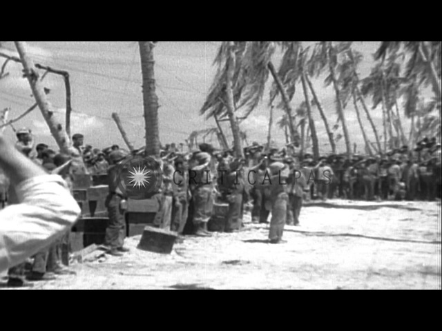 Marines salute the American flag-raising at Tarawa Island, Pacific Ocean. HD Stock Footage