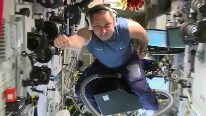 Russian astronaut flying on a vacuum cleaner at ISS