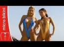 Two micro bikini models in daring slingshot swimsuits beach photoshoot