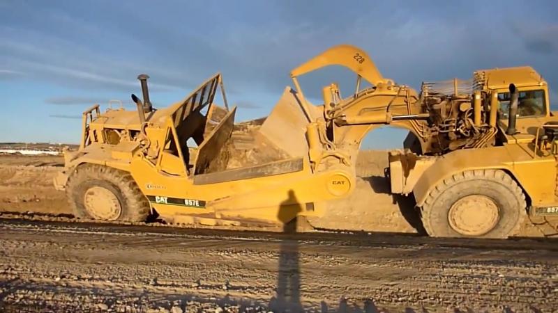 Землеройно-транспортная машина (скрепер) режет грунт под наклоном