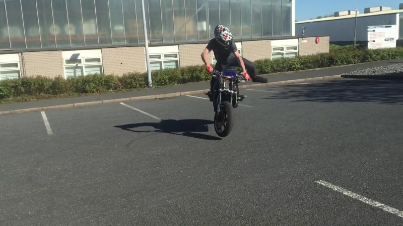 Lad on motorbike skids on front wheel then falls off