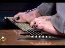 Безрукий музыкант играет ногами на гитаре