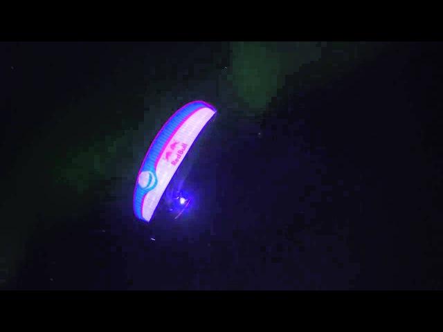 Захватывающий ночной полет на параплане на фоне зеленых волн северного сияния