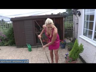 Молодая сексуальная мамка в красном платье наводит порядок во дворе дома не стыдятся соседа