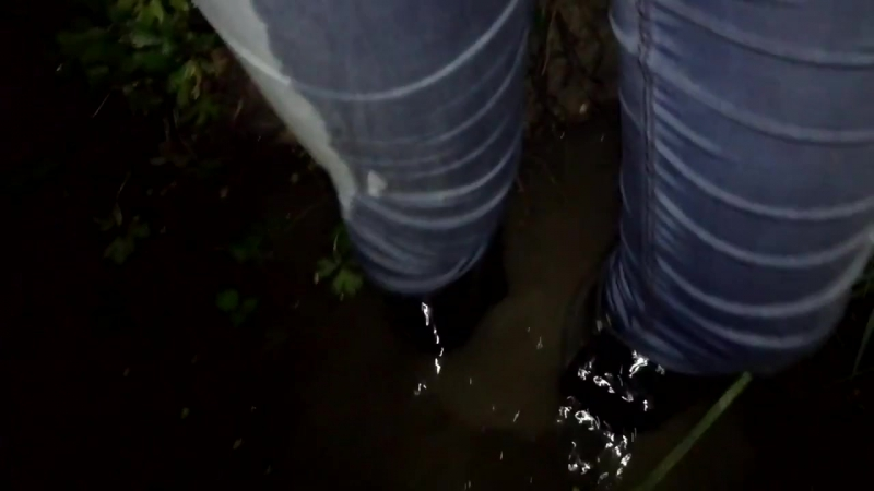 A girl in rubber boots with high heels and wet jeans in the water and mud 1 MO