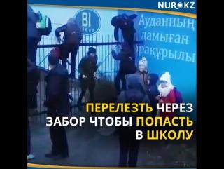 Ученики перелезают через забор со штырями, чтобы попасть в лицей в Астане