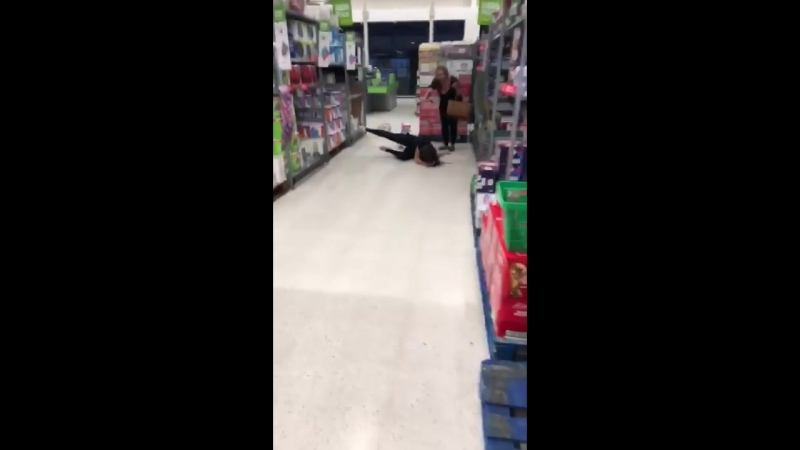 Girl kicks a pile of kitchen towels and falls over