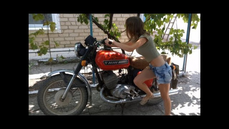 Красивая девушка заводит советский мотоцикл