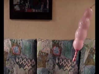 blow to pop a long pink balloon