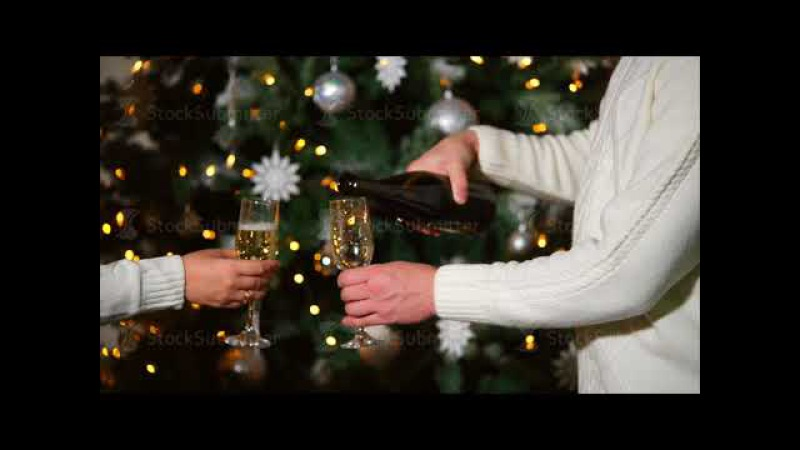 Man and woman are pouring champagne in glasses, standing near Christmas tree