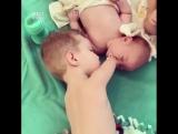 Безрукий маленький мальчик заботится о новорожденном братике