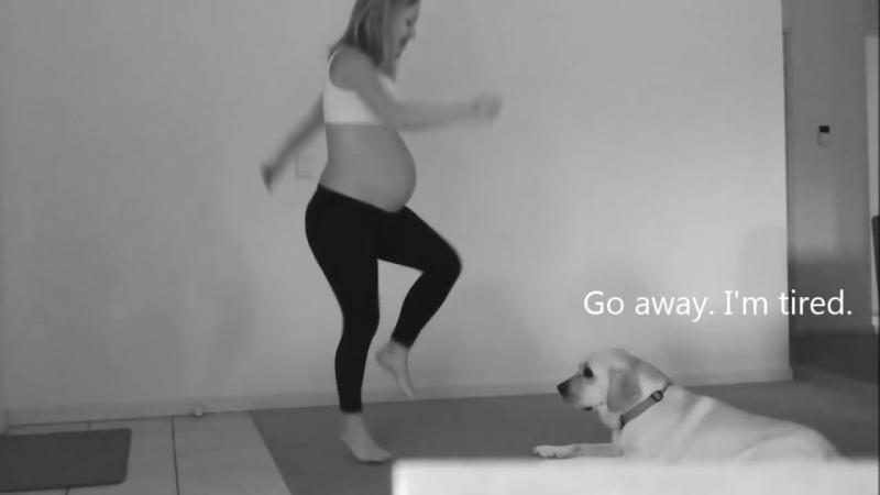 Pregnant woman dancing with Labrador dog
