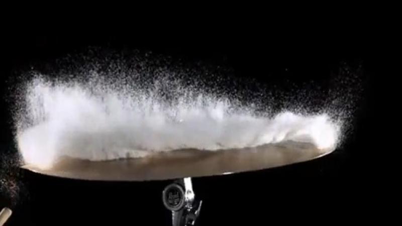 Удар барабанной палочкой по тарелке, на которой насыпан сахар в высокоскоростной съемке.