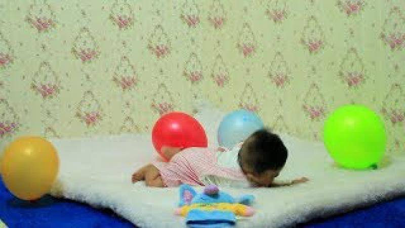 Lihat Usaha Bayi Lucu Meraih Balon Warna Warni dan Boneka