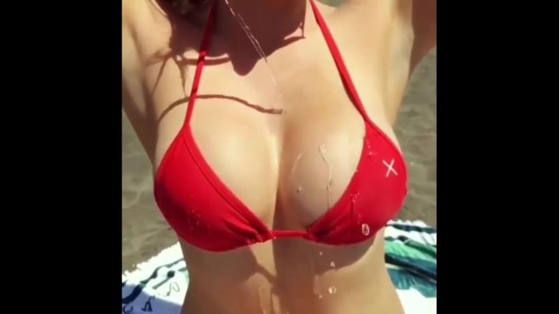 Красивая девушка поливает водой на свои сиськи очень эротично