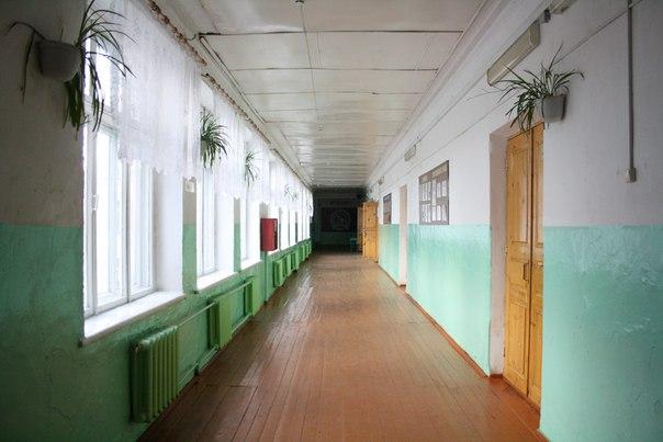 Перспективный вид на коридор второго этажа первой школы.  Недавно заменили все двери в школе на лёгкие лакированные деревянные. В конце коридора висит огромная доска для стен-газеты школьников.