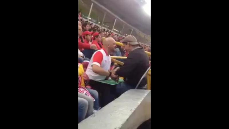 Мужчина руками на маленьком поле показывает слепому другу, как проходит матч