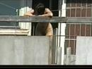 Голая девушка на балконе дома напротив