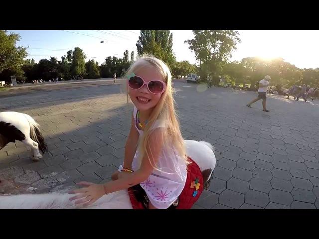 Ева гуляет по парку, катается на пони.