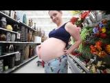 Беременная девушка показывает свой животик в магазине