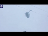 Skiers swing from side to side on chairlift in Austria by strong winds