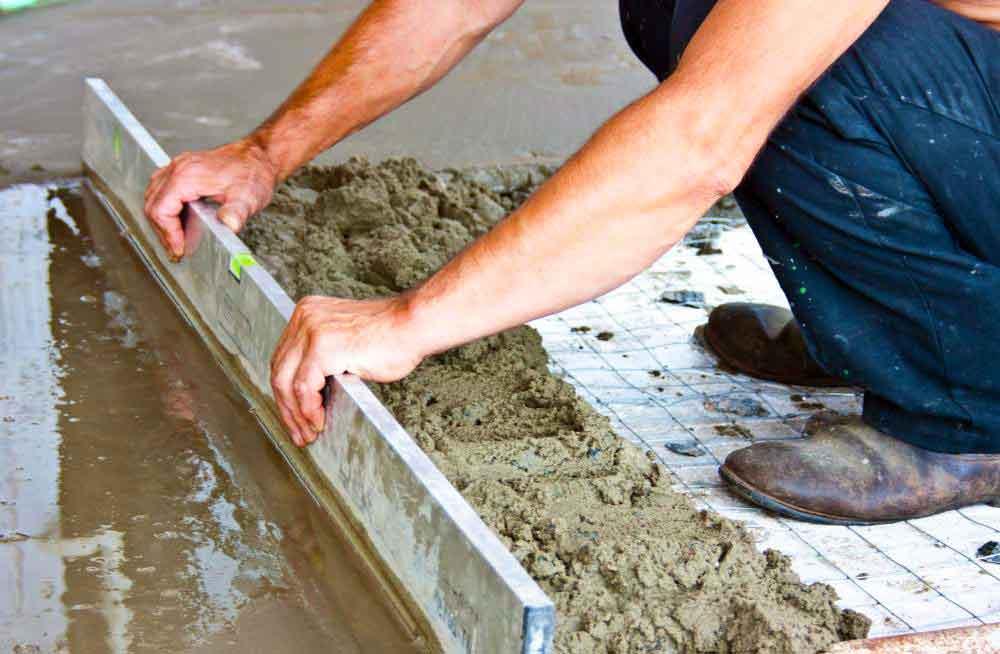 Установщик гипсокартона прикладывает отделочное покрытие к стенке гипсового цемента