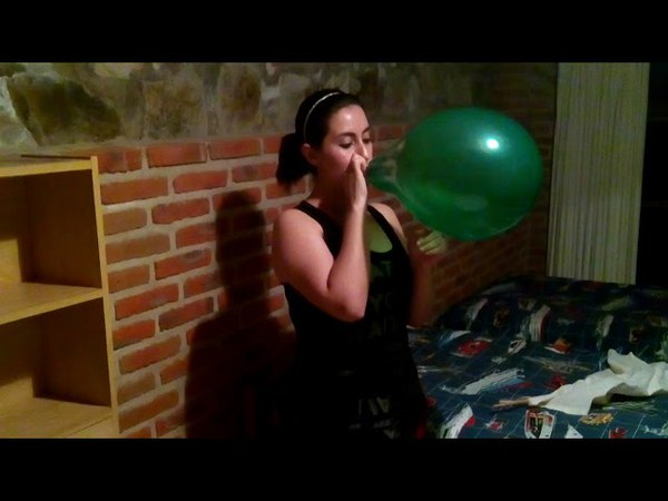 Green balloon blow to pop against wall by girl