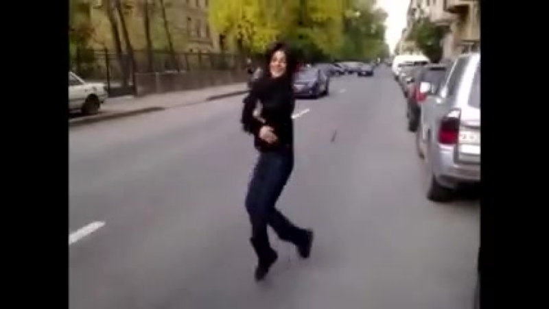 Красивая девушка красиво танцует лезгинку прямо на дороге