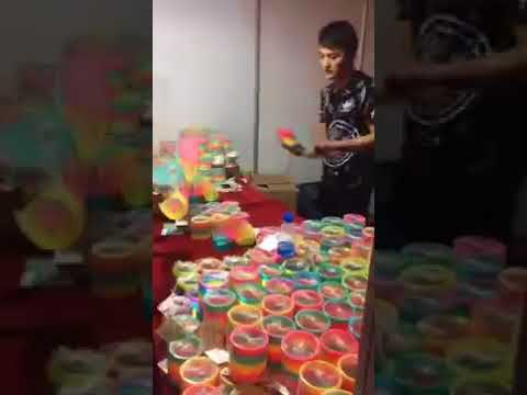 Продавец показывает чудеса владения разноцветной пружинкой