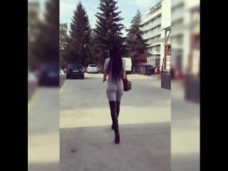Жгучая брюнетка с шикарной попой вышагивает по улице в черных сапогах на высоком каблуке