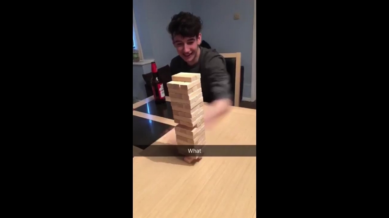 Lad hits Jenga piece from the bottom without knocking it over