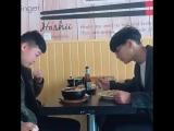 У парня слева прилип рис на щеке, а парень справа показывает ему, что у него там что-то есть на щеке.