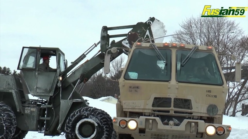U S Military Wheel Loader Loading Snow into a dump truck