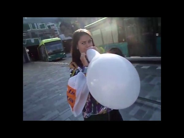 Sweet girl blows to pop a really strong balloon